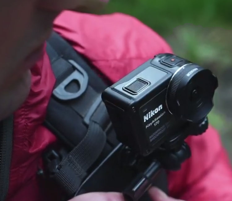 A hiker uses the Backpack Mount Clip to attacth the KeyMission 170 to his backpack strap
