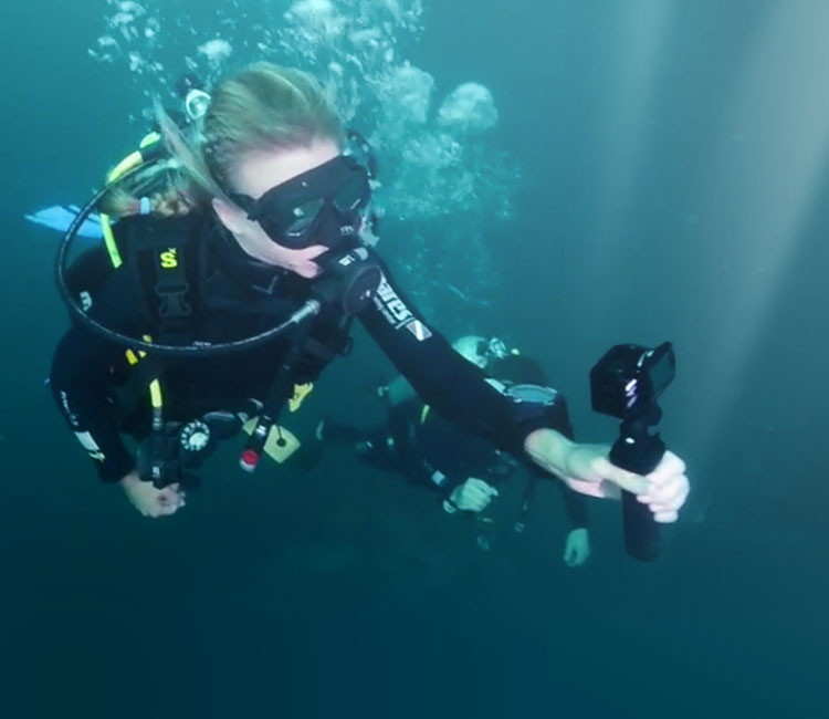Two divers using the KeyMission 170 and accessories to film underwater
