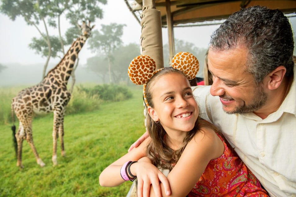 Father and daughter watch a giraffe in the Harambe Wildlife Preserve.