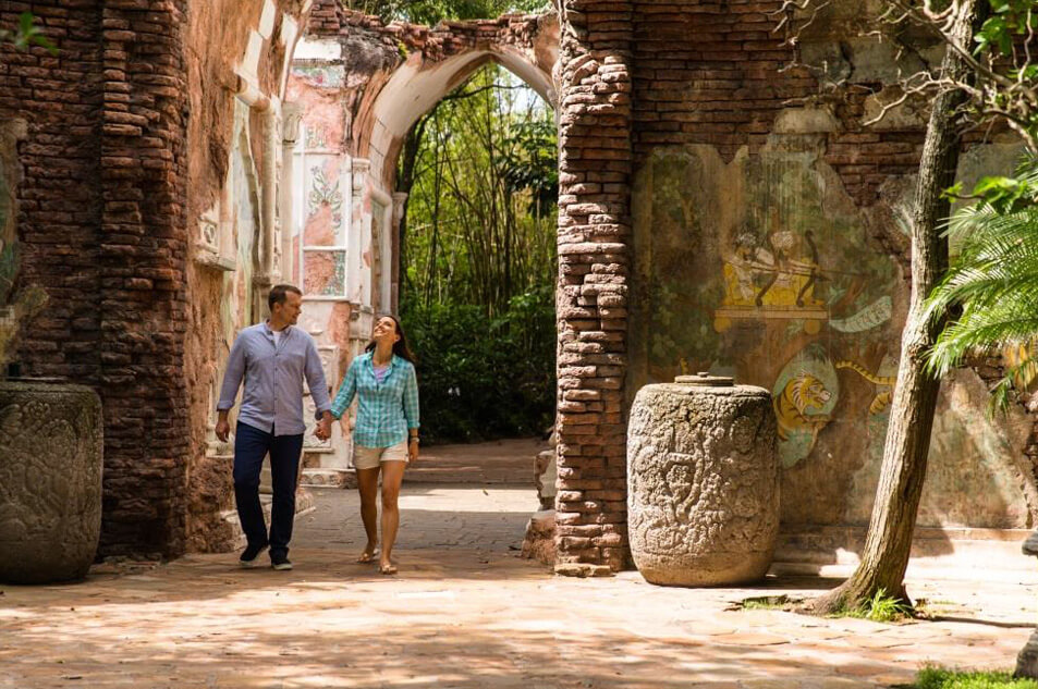 A couple holding hands walking through the Maharajah Jungle Trek.
