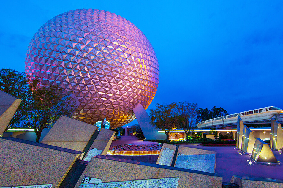 A photo of The Fountain at night with Spaceship Earth in the background.