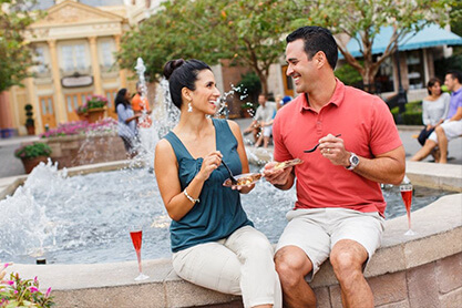 A smiling couple enjoying French cuisine in front of a fountain.