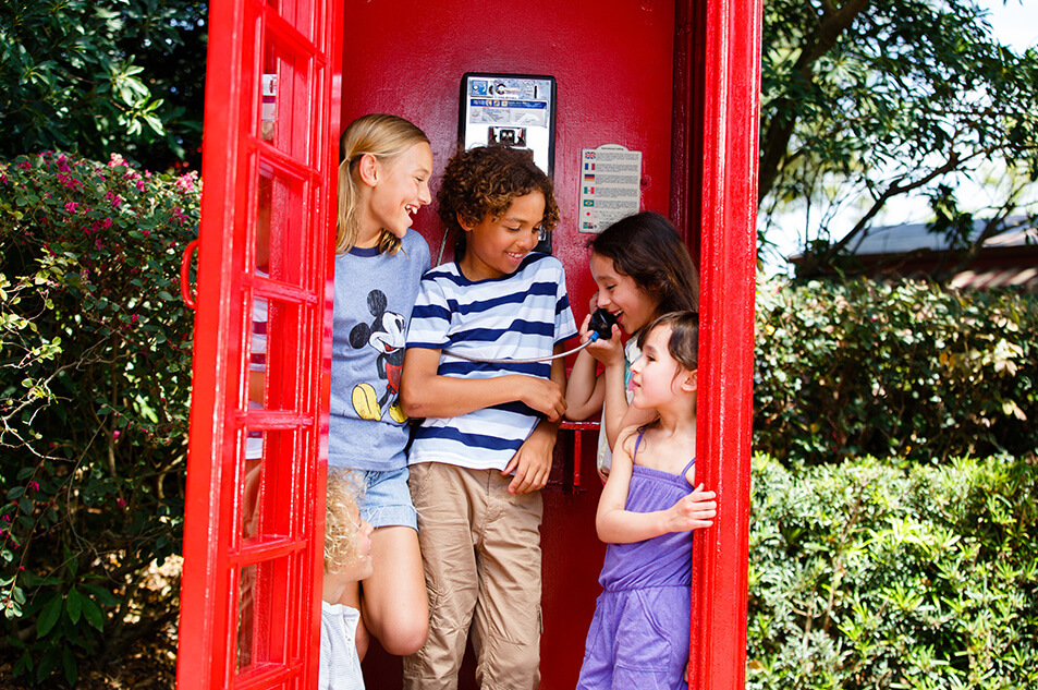 A group of children posing inside of a red phone booth.