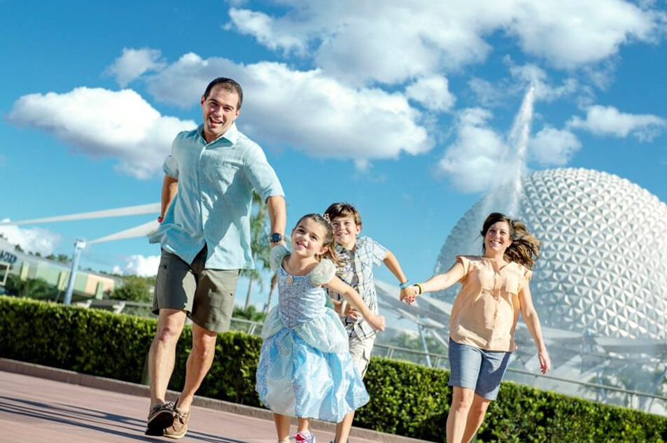 A family running in front of Spaceship Earth.