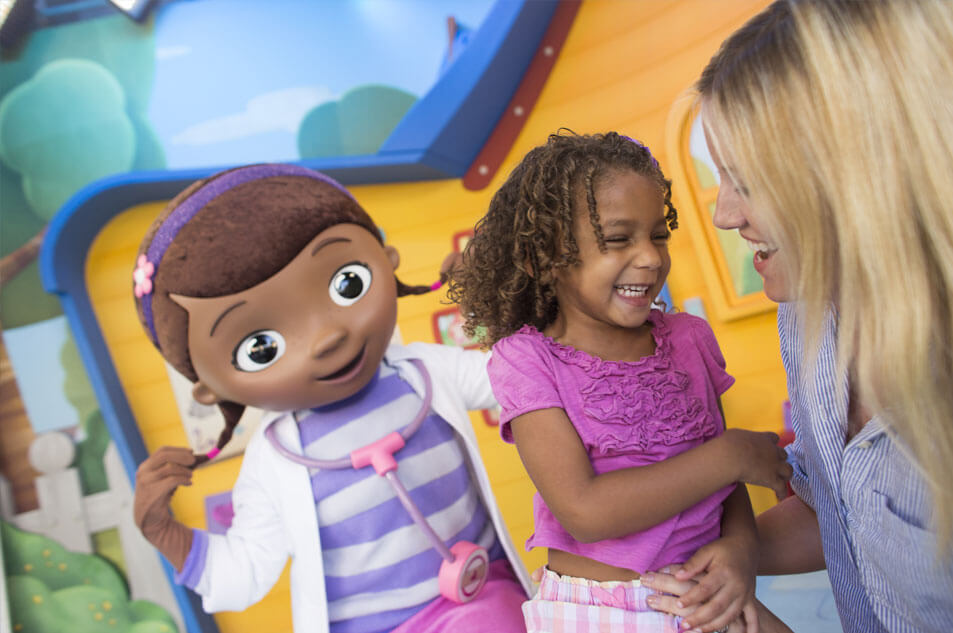 A photo of young girl meeting Doc McStuffins.