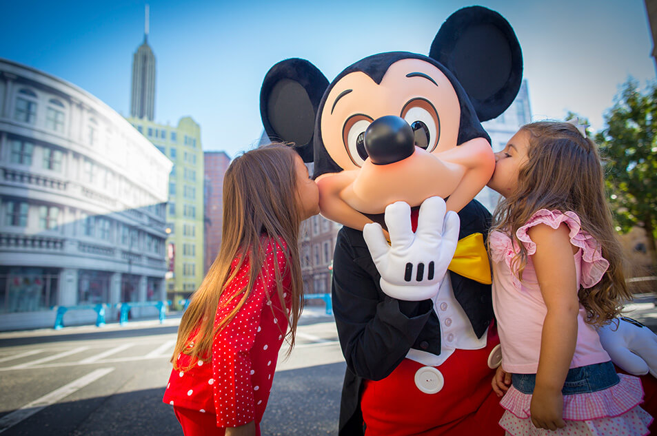 Two little girls posing with Mickey.