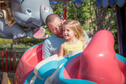 Father and daughter riding Dumbo the Flying Elephant.