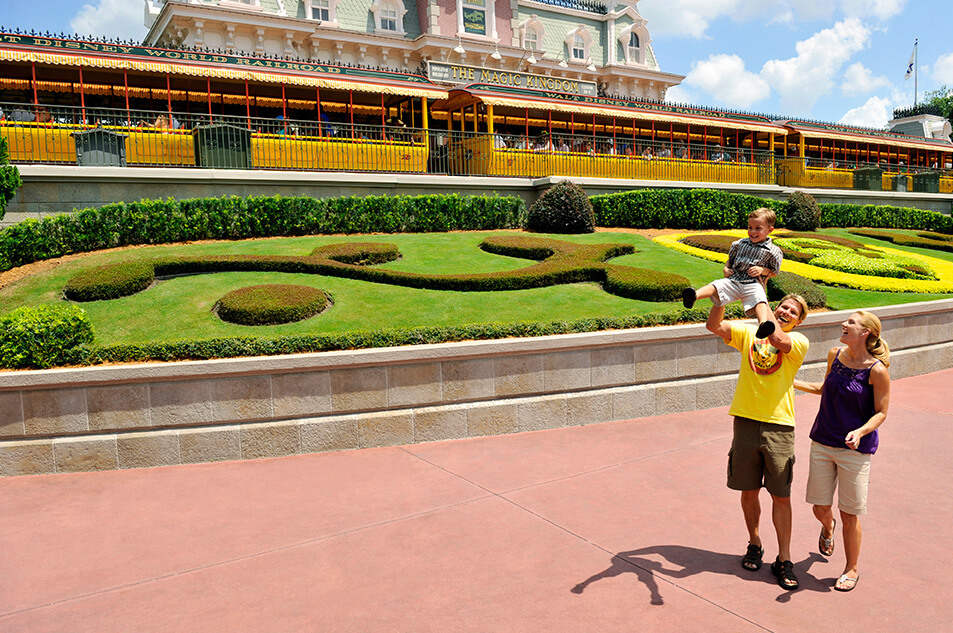 A smiling family in front of Walt Disney World Railroad.