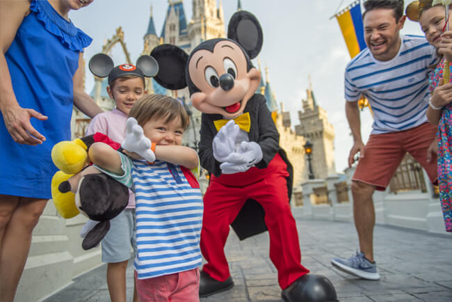 A candid photo of children holding hands with Mickey and jumping.