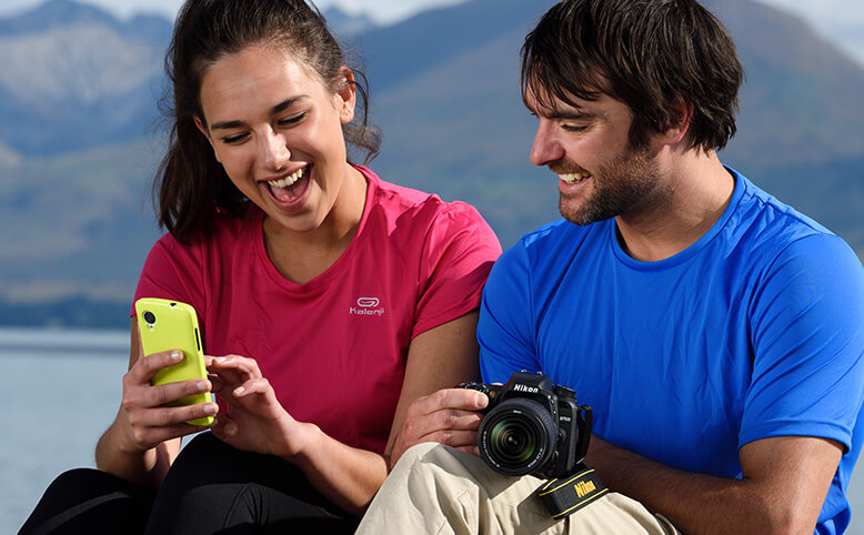 Man and woman smiling while holding a Nikon DSLR and a smartphone