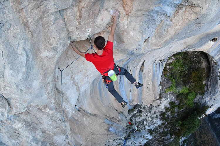 A rock climber hanging on a rock ledge with his hands