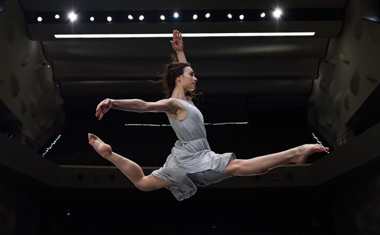 A ballerina leaping on a dark stage
