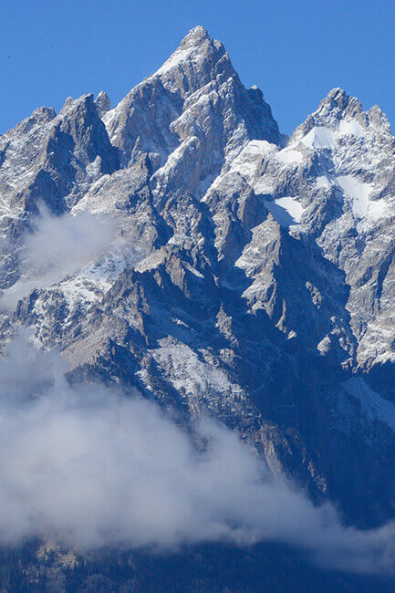 Snowy peaks of a mountain show through the clouds with a bright blue sky in the background
