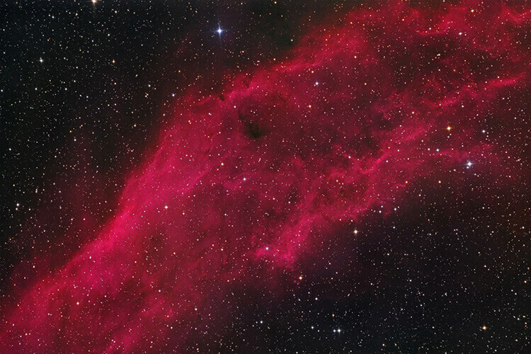 An astrophotography shot of a reddish nebula in the night sky