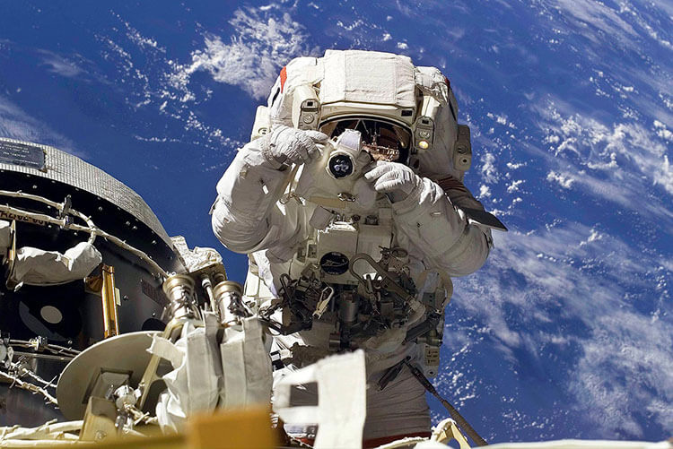 Photo of an astronaut using a Nikon camera in space demonstrating the history of NIKKOR