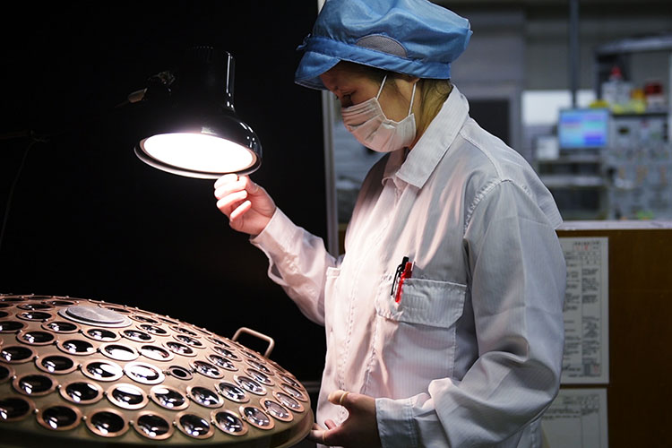 A Nikon employee shines light on a group of NIKKOR lenses to inspect them