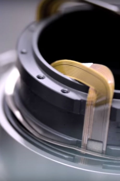 A close up of a NIKKOR lens during assembly