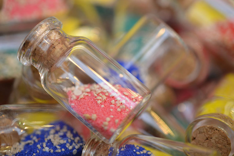 A pile of small glass bottles filled with brightly coloured sand and miniature seashells