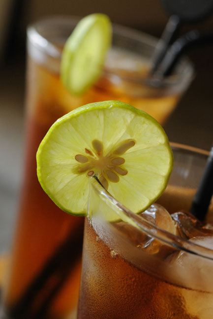 A close up of two glasses of iced tea with a lemon slice on the rim of the glass
