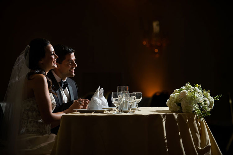 A bride and groom sitting at a wedding table with the lights turned down