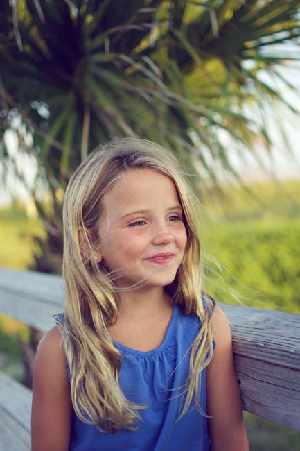 A little girl smiling with a palm tree in the background