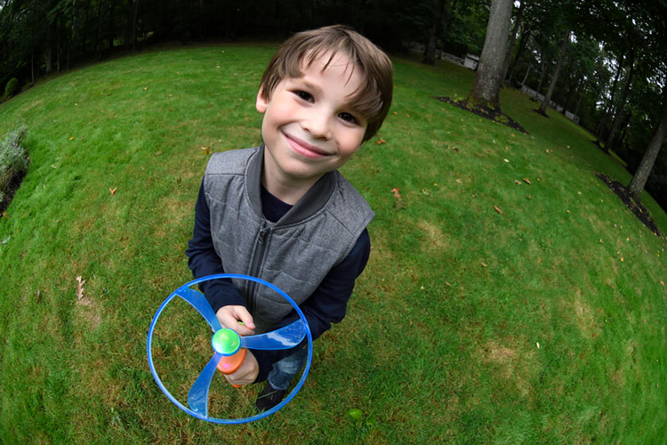 A fisheye effect on a young boy playing with a toy in the yard