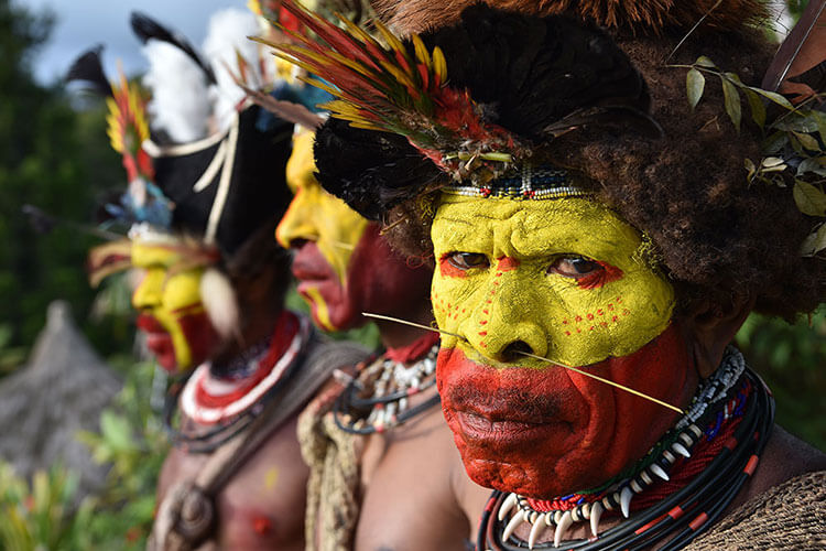 Three tribesmen with their faces painted in bright yellow and red