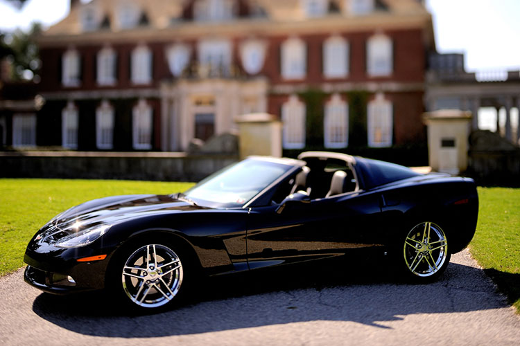 A shiny black sports car sits in front of a large brick house