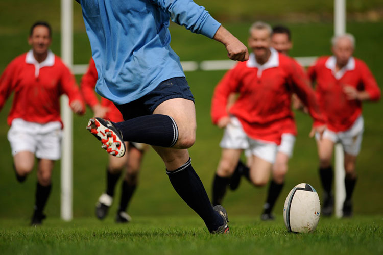 A rugby player in a blue polo gets ready to kick the ball with opponents in red polos running towards him