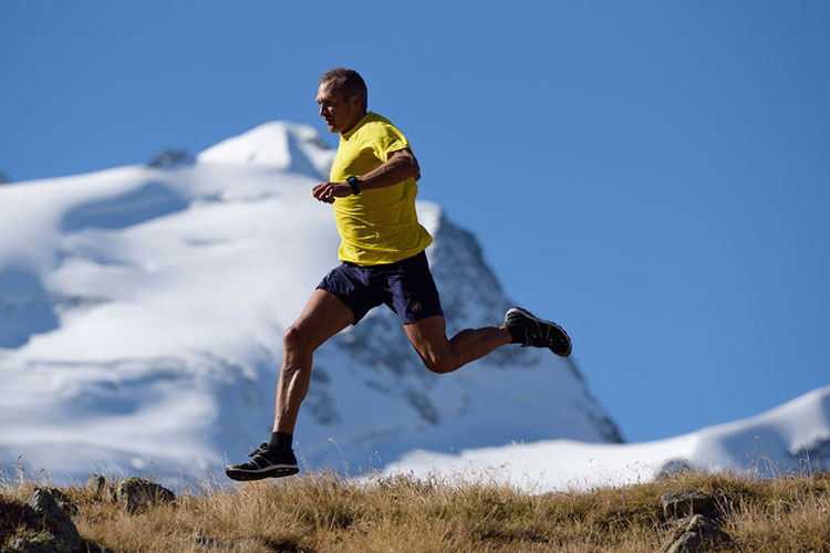 An older man in a yellow shirt and blue shorts sprints across a trail