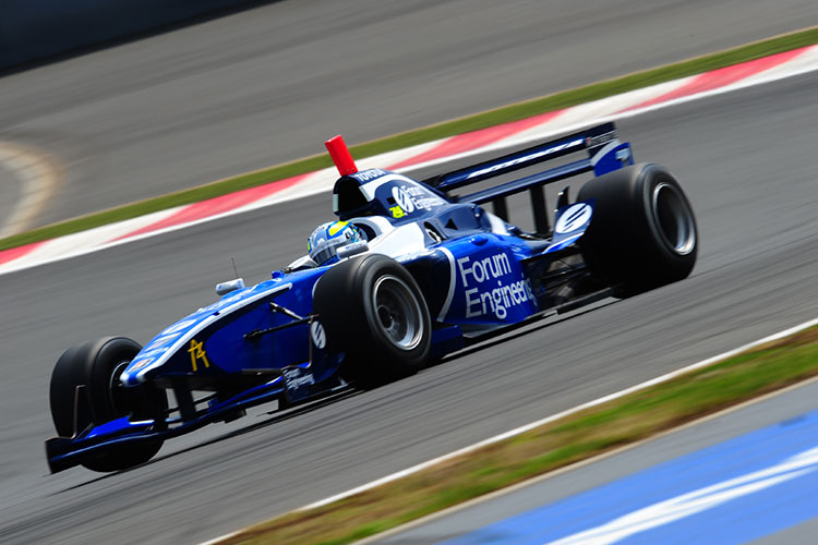 A dark blue formula one race car speeds around the track