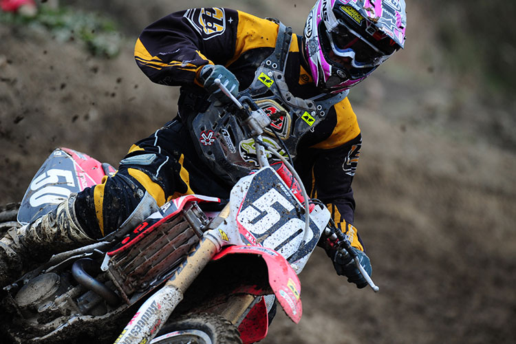 A motocross rider races on a dirt track, flinging up mud
