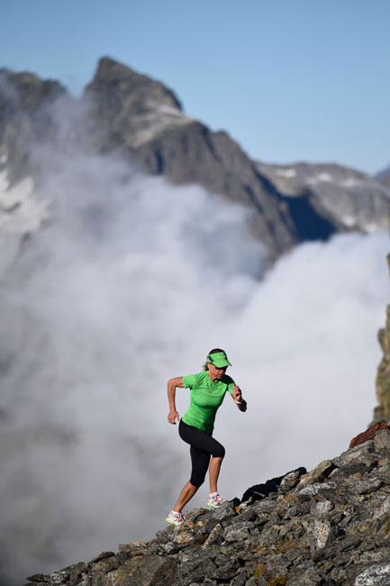 A woman in green athletic grear runs up a rock covered mountain