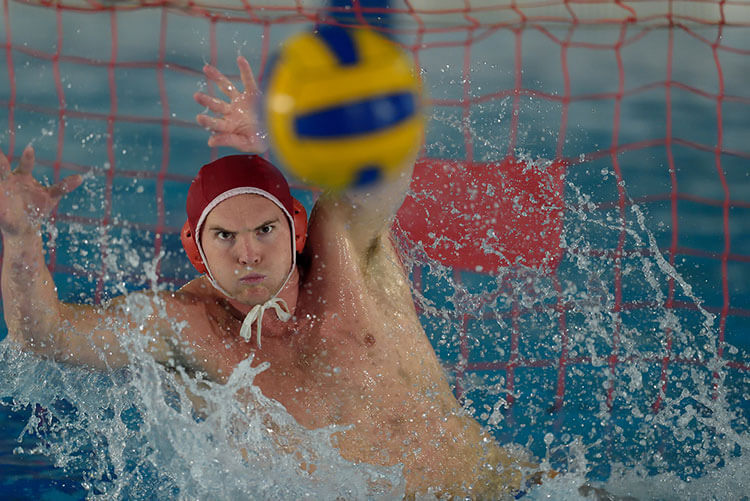 A man jumping to prevent a goal in water polo