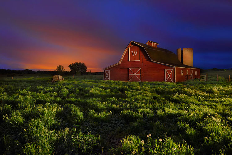A red barn in a green field during sunset