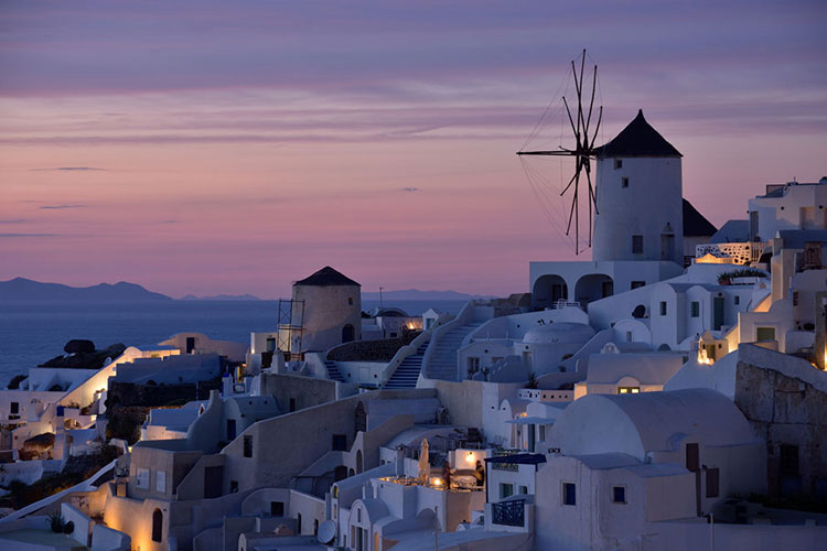 A villiage in Greece with a purple sky in the background