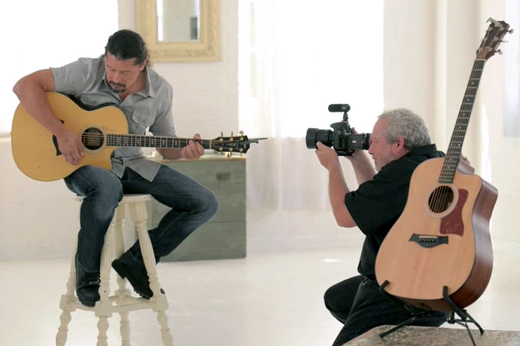 A videographer records a man playing an accoustic guitar