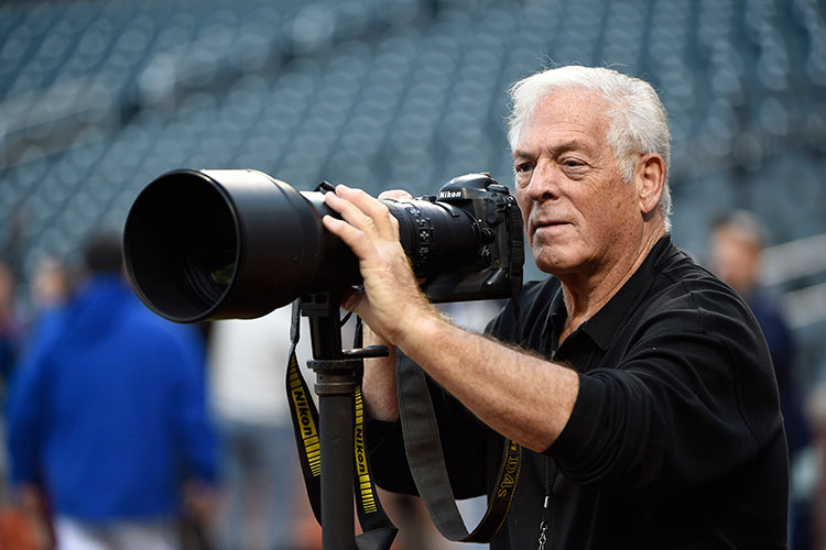 A photographer with a Nikon DSLR and NIKKOR lens inside of a sports stadium
