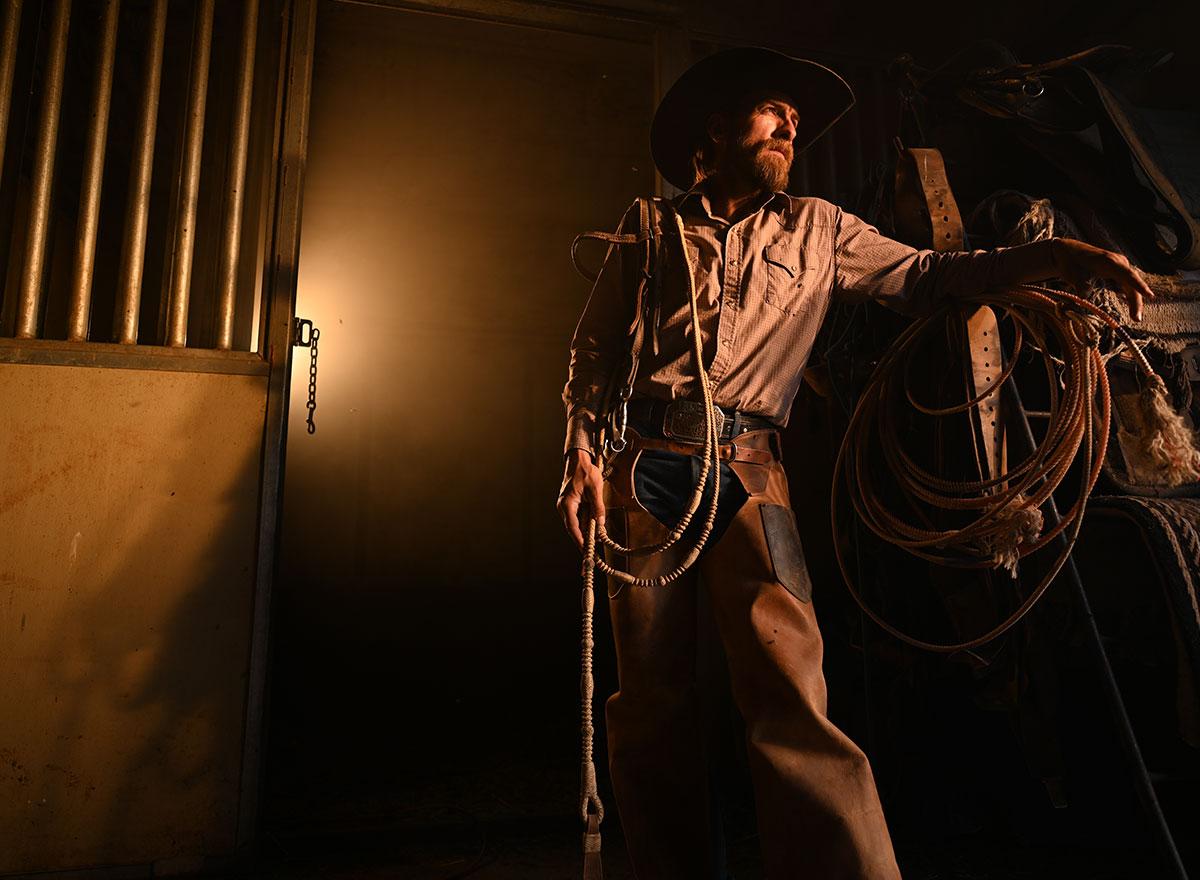 Man dressed as cowboy in low-light
