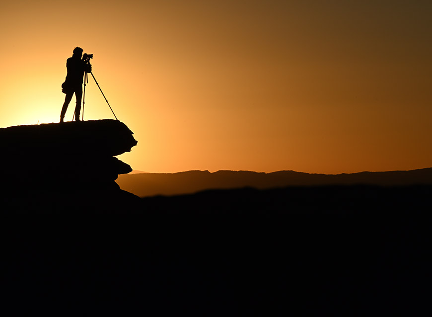 Silhouette of man using camera on tripod
