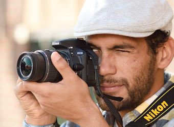Image of a man taking a photograph with a DSLR Camera.