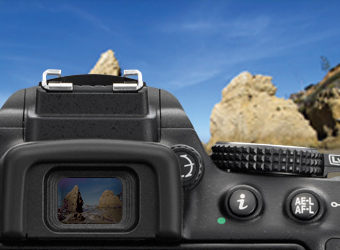 Image of a camera taking a photograph of a valley between two mountains.