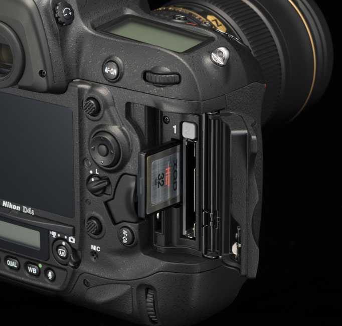 Rear of the Nikon D4S pro level DSLR camera with the door open to show the media card slots and an XQD card half in/half out