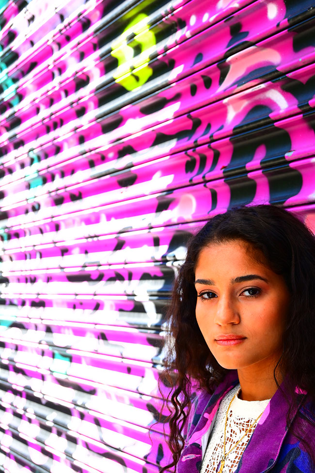 Gabriela Herman photo of a girl against a colorfully painted wall, taken with the Z 50 mirrorless camera using the vivid picture control and super vivid scene mode