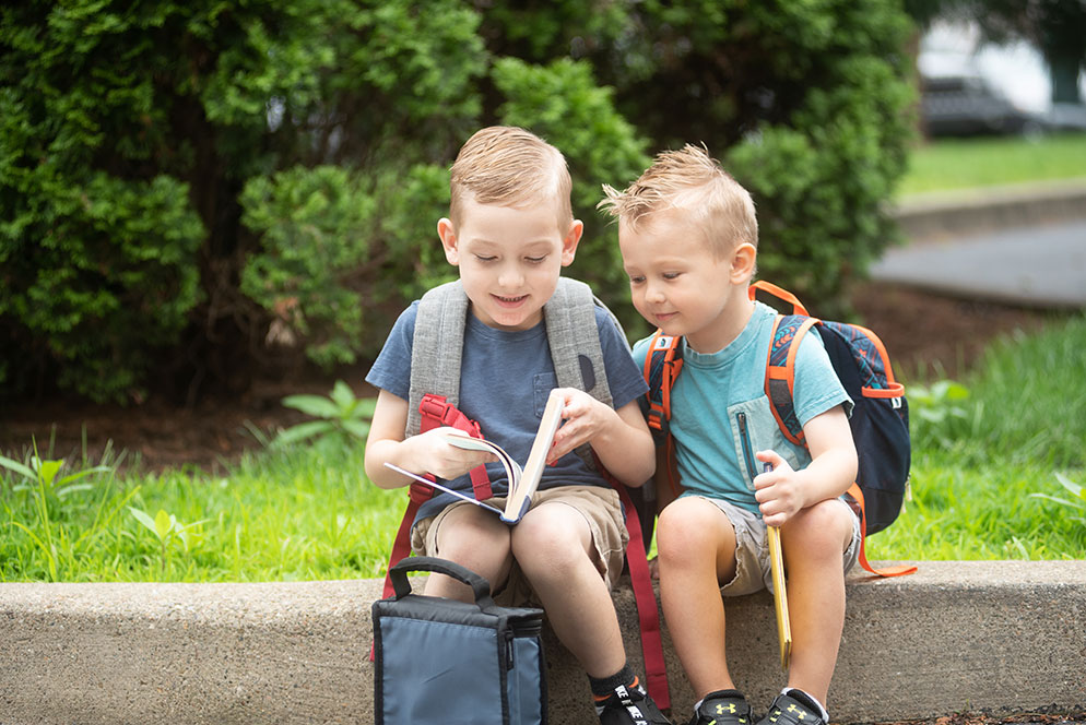 Kathy Wolfe photo of two boys reading a book, while waiting for the school bus