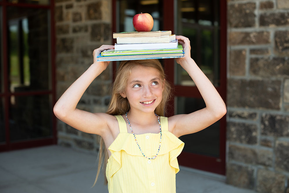 Kathy Wolfe photo of a girl balancing books and an apple on her head.