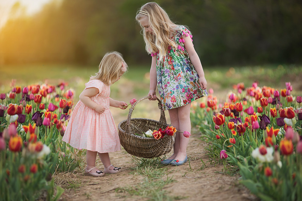 Kathy Wolfe candid photo of two girls picking flowers in a field, holding a basket.
