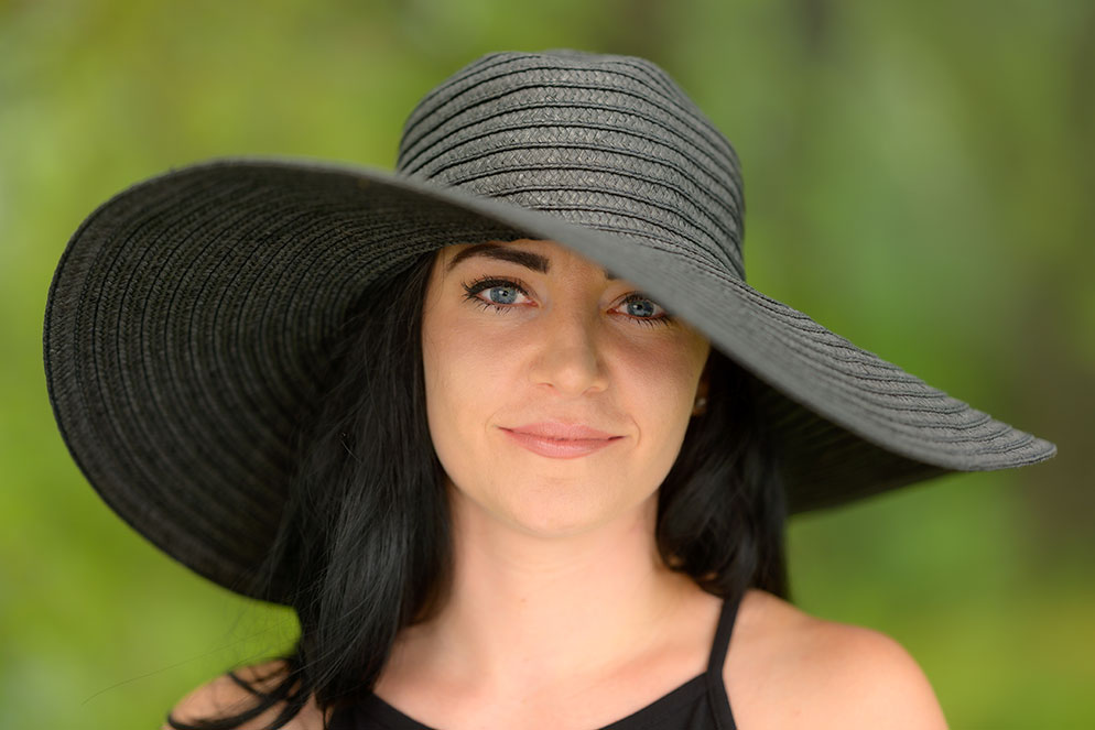 Chris Ogonek photo of a woman wearing a large floppy hat, taken using the NIKKOR Z 85mm f/1.8 S lens.