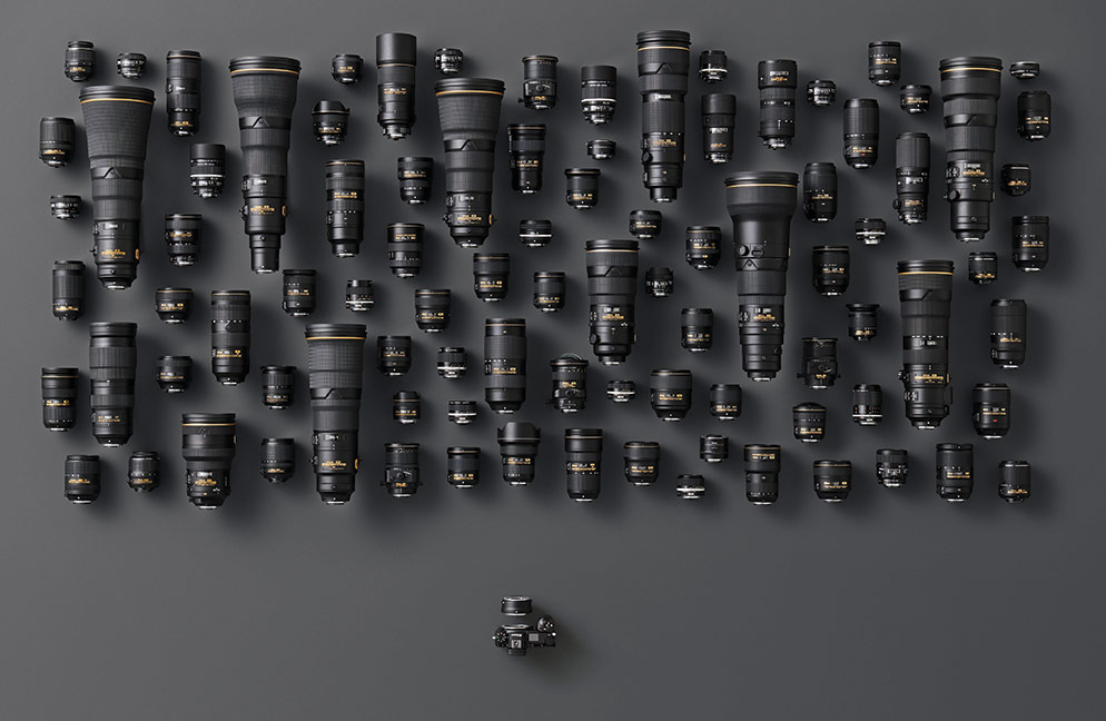 Grouping of dozens of Nikon F mount lenses and a Nikon Z series camera with Mount Adapter FTZ attached showing the breadth of lens compatibility.