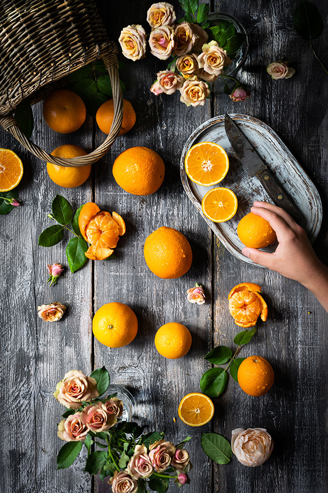 overhead view of a wooden table with a basket, oranges, flowers and a person's hand holding an orange